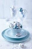 Zilveren en blauwe Kerstmisornamenten in een kop Stock Afbeeldingen