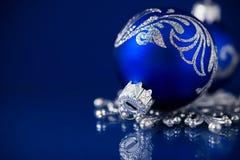 Zilveren en blauwe Kerstmisornamenten op donkerblauwe achtergrond met ruimte voor tekst Royalty-vrije Stock Foto's