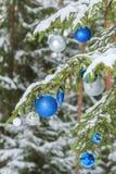 Zilveren en blauwe ornamenten van Kerstmis vertakt de feestelijke briljante snuisterijen zich in openlucht op sneeuwspar Stock Fotografie