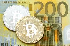Zilveren en gouden bitcoin op 200 euro bankbiljetachtergrond Stock Foto's