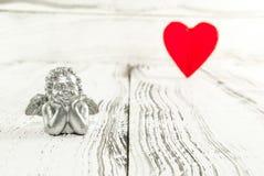 Zilveren engel en rood hart op witte houten achtergrond royalty-vrije stock afbeelding