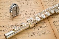 Zilveren fluit en zakmetronoom op een oude muziekscore Royalty-vrije Stock Foto's