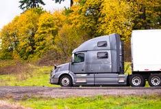 Zilveren grote installatie semi vrachtwagen met droge bestelwagen semi aanhangwagen die op aut gaan Stock Foto