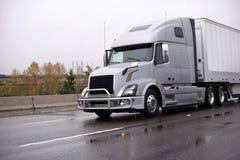 Zilveren grote installatie semi vrachtwagen met traliewerkwacht die droge bestelwagen vervoeren stock foto's