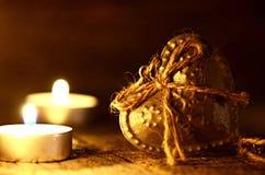 Zilveren hart op een houten lijst met decoratie Rood nam toe Liefde Gift Ilustration op een natuurlijke achtergrond kaarsen en br Stock Afbeeldingen