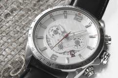 Zilveren horloge op canvas Stock Afbeeldingen