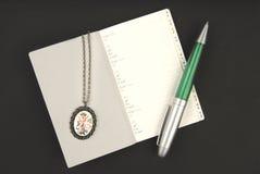 Zilveren juwelen, pen en notitieboekje Stock Foto's