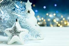 Zilveren Kerstmisster en sparrentak met slinger tegen B Stock Foto