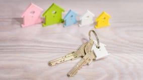 Zilveren Keychain die op houten Oppervlakte voor miniatuursymbool van diverse gekleurde huizen leggen die in lijn blijven stock afbeeldingen