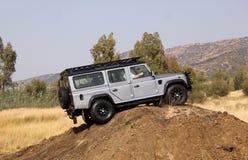 Zilveren Land Rover Defender 110 SW op 4x4 Cursus Royalty-vrije Stock Foto's