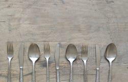 Zilveren lepels, vorken en messen op oude, roestige, houten achtergrond Stock Foto