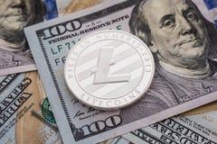 Zilveren Litecoin-muntstuk op de achtergrond van dollarsbankbiljetten Bedrijfs en technologieconcept Digitaal mede munt fysiek me Royalty-vrije Stock Foto