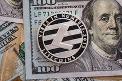 Zilveren Litecoin-muntstuk op de achtergrond van dollarsbankbiljetten Bedrijfs en technologieconcept Digitaal mede munt fysiek me Royalty-vrije Stock Afbeelding