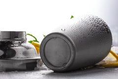 Zilveren metaal vochtige die schudbeker op een vage witte achtergrond, een verse munt en een sappige citroen op een wit tafelklee Stock Afbeelding