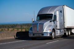 Zilveren moderne grote installatie semi vrachtwagen met aanhangwagen die op snelweg lopen Royalty-vrije Stock Fotografie