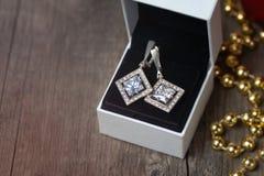 Zilveren oorringen met fianits in witte giftdoos Royalty-vrije Stock Foto
