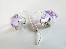 Zilveren oorringen met lilakristal Royalty-vrije Stock Foto's