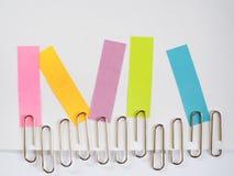 Zilveren paperclippen en kleurrijke kleverige nota's over een witte backgrou Stock Foto's