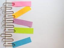 Zilveren paperclippen en kleurrijke kleverige nota's over een witte backgrou Royalty-vrije Stock Afbeeldingen