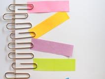 Zilveren paperclippen en kleurrijke kleverige nota's over een witte backgrou Royalty-vrije Stock Foto