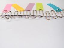 Zilveren paperclippen en kleurrijke kleverige nota's over een witte backgrou Royalty-vrije Stock Foto's