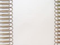 Zilveren paperclippen op een witte achtergrond met vrije tekstruimte Royalty-vrije Stock Afbeeldingen