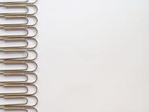 Zilveren paperclippen op een witte achtergrond met vrije tekstruimte Stock Fotografie
