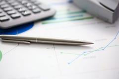 Zilveren pen en calculator op het werk klaar om worden gebruikt stock foto