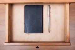 Zilveren pen en zwart notitieboekje in open lade Stock Fotografie