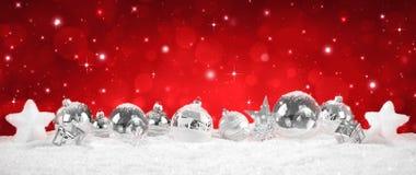 Zilveren Snuisterijen op sneeuw - rood Royalty-vrije Stock Afbeeldingen