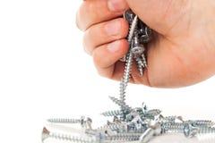 Zilveren spijkers in menselijke hand Stock Afbeelding