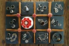 Zilveren vrouwen` s juwelen in 11 vierkanten op een zwarte leisteen royalty-vrije stock foto