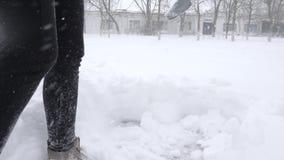 Zim pracy, mężczyzna z łopatą w rękach czyścą podwórze od śniegu podczas opadu śniegu zbiory wideo