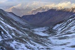 Zim wysokich gór droga: skłony wzgórza zakrywają z śniegiem droga wiatry jak faborek w tle, są ogromnym da Obraz Royalty Free