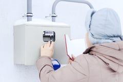 Zima, śnieg, zimno dziewczyna inżynier pracownik nagrywa czytania ciśnieniowi wymierniki i czujniki Lokalizują fotografia stock