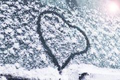 Zima, śnieg, zimno na samochodu szkle malujący serce tam tonuje obraz stock