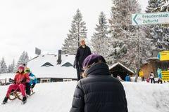 Zima dzień z śnieżnymi i szczęśliwymi dzieciakami pochodzi sledding pomyje Zdjęcia Royalty Free