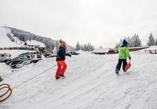 Zima dzień z śnieżnymi i szczęśliwymi dzieciakami wspina się sledding skłon Obrazy Stock