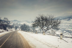 Zima krajobraz, śnieg zakrywał drogę w górach z drzewami Obrazy Royalty Free