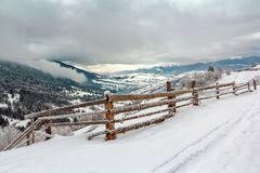 Zima krajobraz w górze z drewnianym ogrodzeniem w foregr Zdjęcie Royalty Free