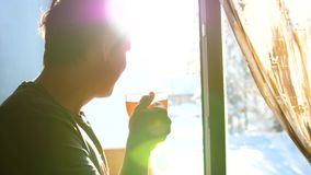 Zima mroźny dzień Facet stoi przy okno i pije gorącej herbaty wcześnie rano zdjęcie wideo