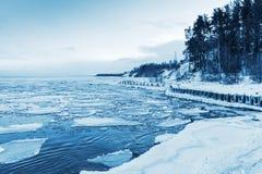 Zima nabrzeżny krajobraz z spławowym lodem i zamarzniętym molem Fotografia Stock