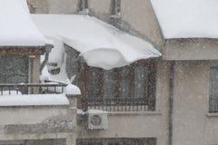 Zima Niebezpieczny śnieg spada od dachów budynki Zima z ciężkim opadem śniegu Lodowaci dachy Niebezpieczni sople nad droga zdjęcie royalty free