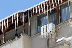 Zima Ogromni niebezpieczni lodowi sople wieszają nad zagrożeń zdrowie uliczny życie ludzie wiesza od dachu budynek i obraz royalty free