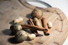 Zima orzechów włoskich cynamonowi kije kłama na drewnianej desce w ciepłym lekkim zbliżeniu fotografia royalty free