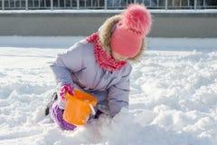 Zima plenerowy portret ono uśmiecha się i bawić się z śniegiem dziecko dziewczyna, jaskrawy pogodny zima dzień obraz royalty free