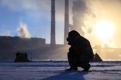 Zima połów, mężczyzna pasja, rybaka chwyta ryba na zamarzniętej rzece przeciw tłu fabryk drymby przy zmierzchem obrazy stock
