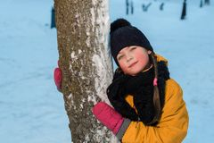 Zima portret ładna mała dziewczynka blisko drzewa dziecko jest ubranym zima kapelusz zdjęcia royalty free