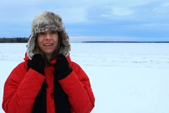 Zima portret kobieta jest ubranym lotnictwo kapelusz owłosioną czerwieni kurtkę i zdjęcie royalty free
