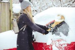 Zima portret młodej kobiety cleaning śnieg od samochodu Piękno blondynki modela dziewczyna śmia się śnieg i radośnie czyści Beaut obrazy royalty free